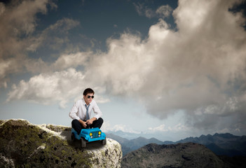 concept of success - uomo con macchinina in vetta alla montagna