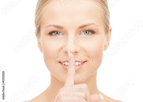 happy woman with finger on lips