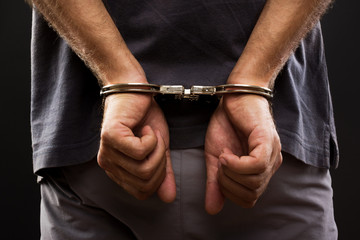 Close-up. Arrested man handcuffed