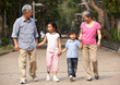 Chinese Grandparents Walking Through Park With Grandchildren