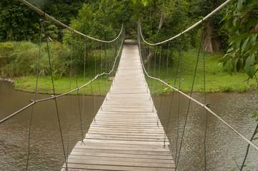 Wood hanging bridge across river in forest.