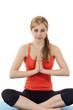 junge sitzende frau bei yoga übungen vor weißem hintergrund