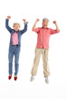 Studio Shot Of Chinese Senior Couple Jumping In Air