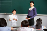 Pupil And Teacher Standing By Blackboard In Chinese Classroom