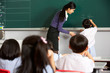 Male Pupil Writing On Blackboard In Chinese Classroom