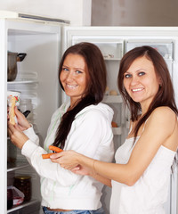 women putting food   into refrigerator