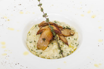 photo of delicious risotto dish with herbs and mushrooms on whit