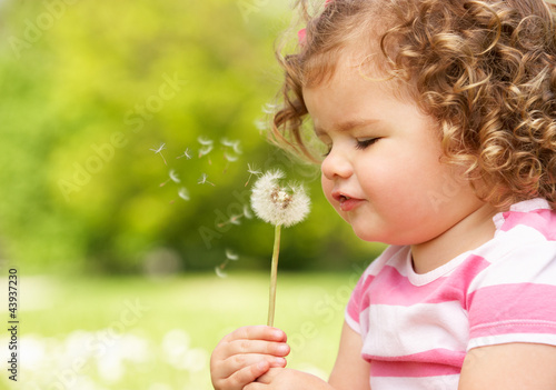 Young Girl In Summer Dress Sitting In Field Blowing Dandelion