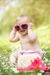 Baby Girl In Summer Dress Sitting In Field Wearing Sunglasses