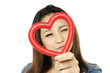 Portrait of a cute young female holding a red heart