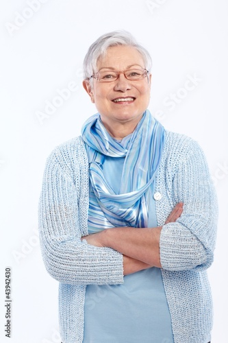 Smiling elderly lady standing arms crossed