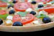 Pizza mit Feta, Tomaten, Oliven und Ruccola