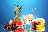 Milk shakes with fruit on blue background close-up