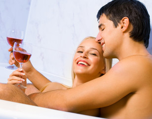 Couple with red wine at bathroom