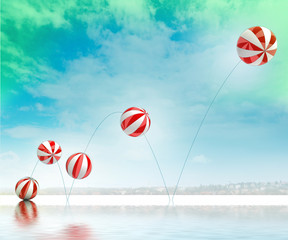 five jumping white red striped inflatable balls on beach