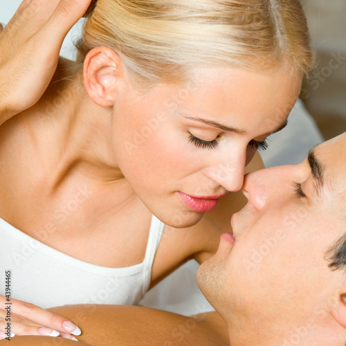 Young kissing cheerful couple