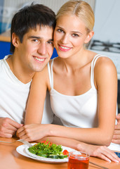 Cheerful couple with vegetarian salad at home