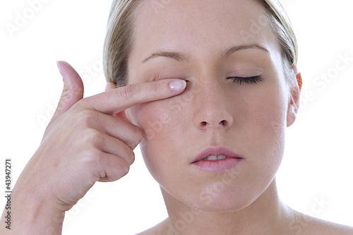 Femme se frotte l'oeil
