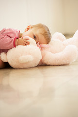 Baby Girl Cuddling Pink Teddy Bear At Home