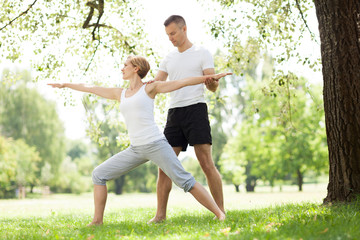 Couple practicing yoga in the park