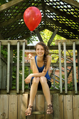 Teen holding a red balloon