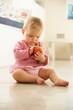 Baby Girl Sitting On Floor Looking At Apple