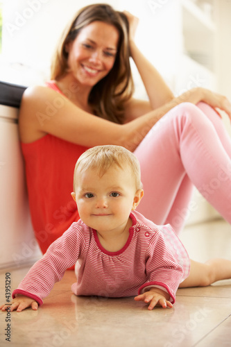 Mother Sitting With Baby Daughter At Home