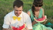 Young couple eating watermelon at picnic, closeup view