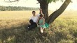 Young couple hugging below the tree on the meadow