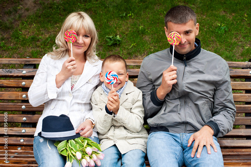 Funny family with toddler son having fun with candies on bench i