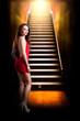 junge brünette im roten Minikleid am Fuße einer Treppe