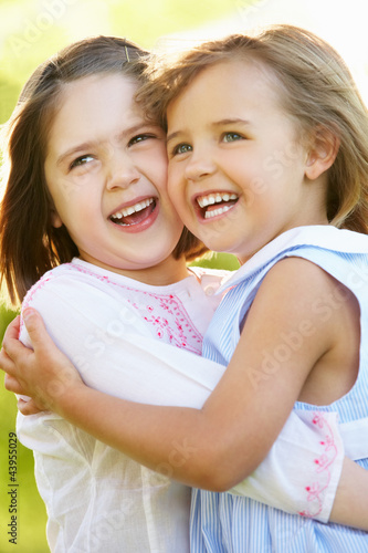 Two Young Girls Giving One Another Hug In Summer Field
