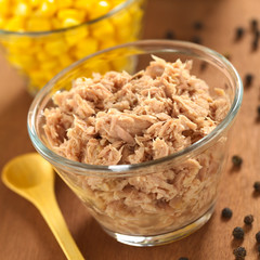 Canned tuna in glass bowl with sweet corn in the back