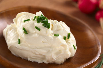 Fresh cream cheese spread on wooden plate with chives