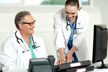 Smiling medical team working on computer
