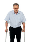 Angry aged man with crutches looking at you