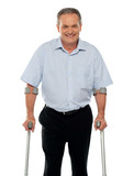 Senior man standing with support of crutches