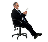 Well dressed corporate male holding wireless tablet