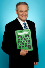 Senior executive posing with big green calculator