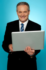 Smiling aged executive holding laptop