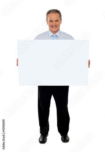 Confident businessman holding blank billboard