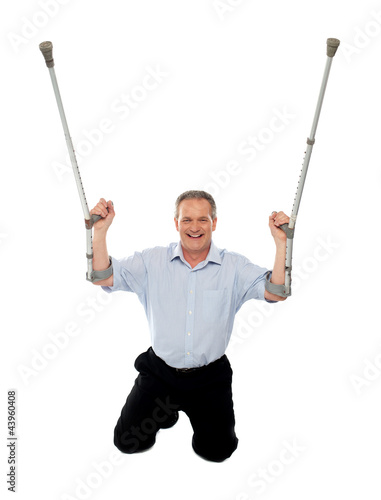 Cheerful senior man holding crutches upwards