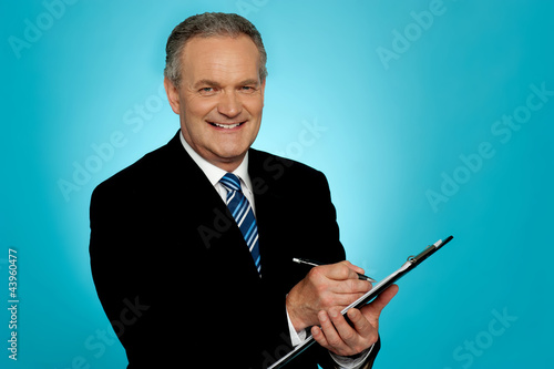 Attractive senior man writing on clipboard