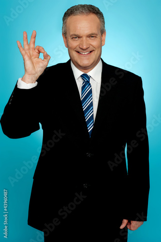 Experienced businessman showing okay sign