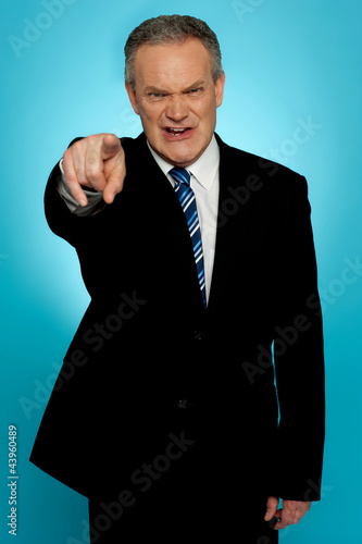 Angry senior businessman pointing finger at you