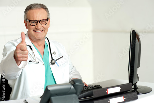 Smiling doctor gesturing thumbs up to camera