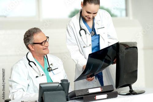 Team of two doctors reviewing x-ray report