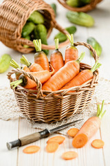 Fresh carrot in the basket with cucumbers