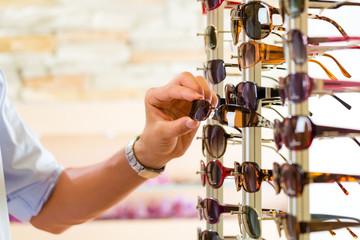 Junger Mann beim Optiker kauft Brille