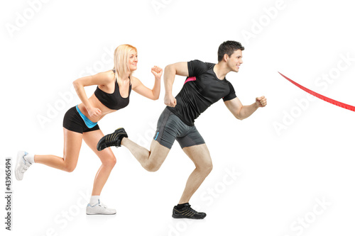 Male and female running towards finish line